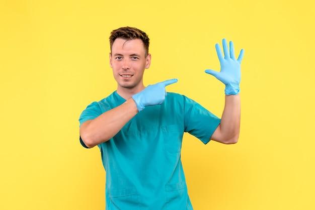 Вид спереди мужчины-врача с синими перчатками на желтом этаже больницы медицинские эмоции