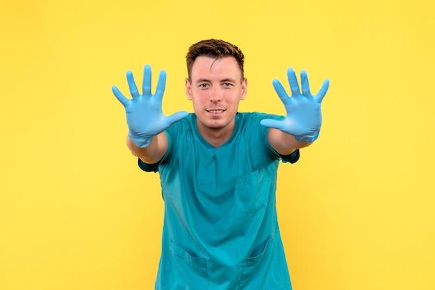 黄色の壁に青い手袋と男性医師の正面図