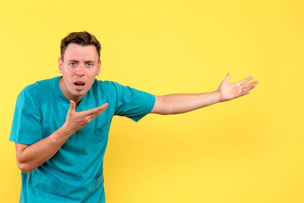 노란색 벽에 혼란스러운 표정으로 남성 의사의 전면보기