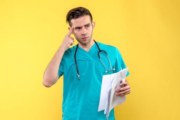 黄色の壁に文書と男性医師の正面図