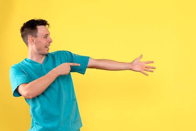 노란색 벽에 흥분된 표정으로 남성 의사의 전면보기