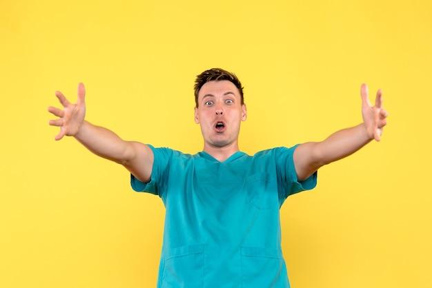 노란색 벽에 흥분된 얼굴로 남성 의사의 전면보기