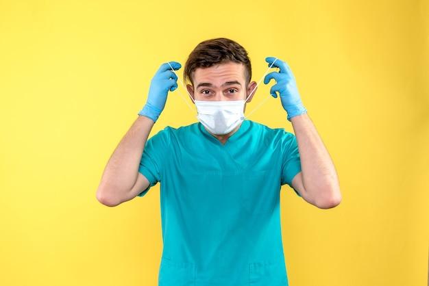 黄色の壁に手袋とマスクを持つ男性医師の正面図