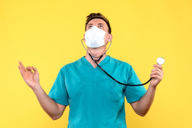 노란색 벽에 마스크와 안압계와 남성 의사의 전면보기