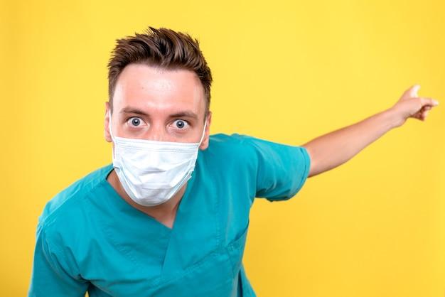 黄色の壁に滅菌マスクと男性医師の正面図