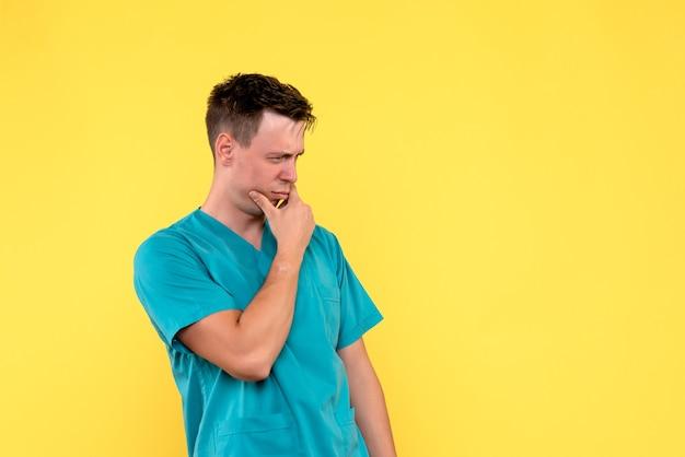 노란색 벽에 생각 얼굴을 가진 남성 의사의 전면보기