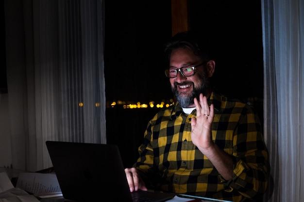 男性従業員の正面図は、オンラインイベントブリーフィングでさまざまな同僚とビデオ通話で話し、男性労働者は夜に自宅で現代のラップトップで同僚とグループ会議を行います