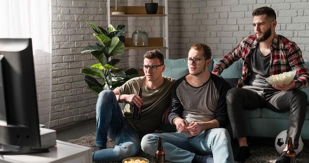 맥주와 축구와 함께 tv에서 스포츠를 보는 남자 친구의 전면보기