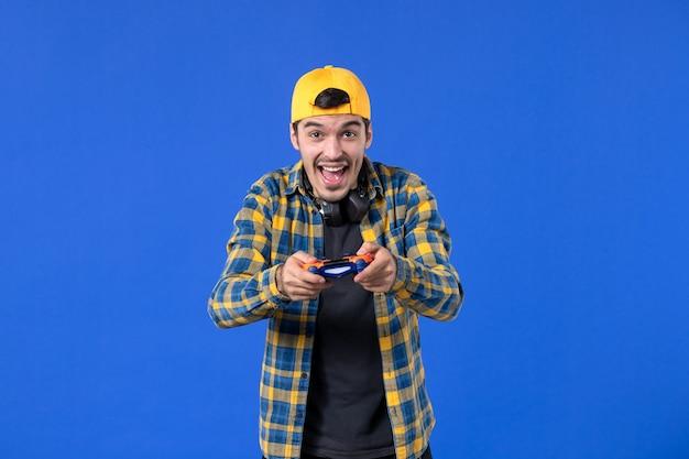 青い壁にオレンジ色のゲームパッドを持つ男性ゲーマーの正面図