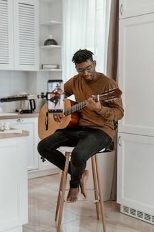 집에서 기타를 연주하고 스마트 폰으로 녹음하는 남성 음악가의 전면보기