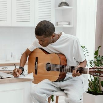집에서 기타를 연주하고 가사를 쓰는 남성 음악가의 전면보기
