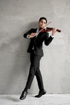 Вид спереди мужской музыкант танцует и играет на скрипке