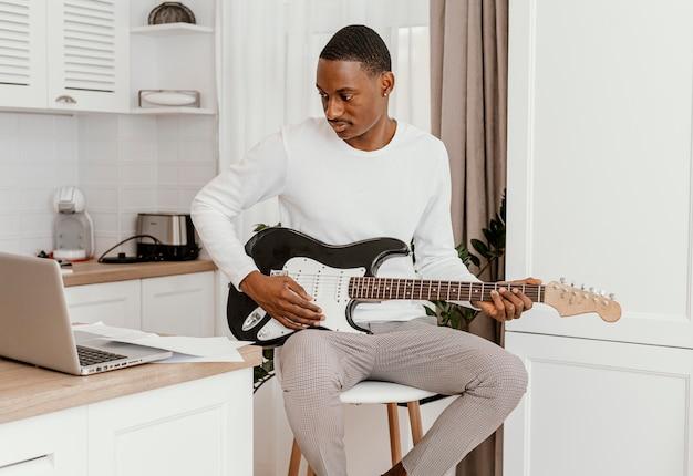 Вид спереди музыканта-мужчины, играющего на электрогитаре и смотрящего на ноутбук