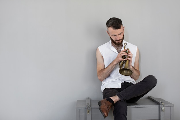 Вид спереди мужского музыканта с корнетом и копией пространства