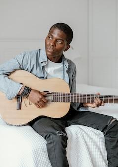 침대에 기타와 함께 남성 음악가의 전면보기