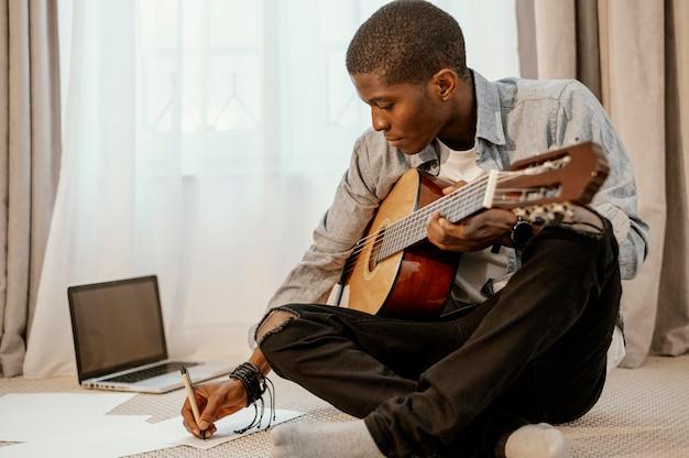 침대와 노트북에 기타와 함께 음악을 쓰는 남성 음악가의 전면보기