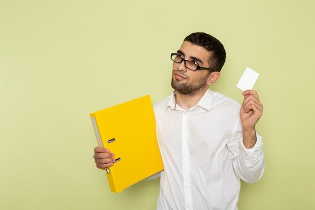 緑の壁にカードとファイルを保持している白いシャツの男性サラリーマンの正面図