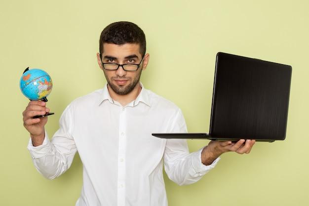 彼のラップトップと緑の壁に小さな地球儀を保持している白いシャツを着た男性サラリーマンの正面図