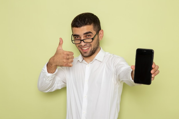 Вид спереди мужского офисного работника в белой рубашке, держащего смартфон на зеленой стене