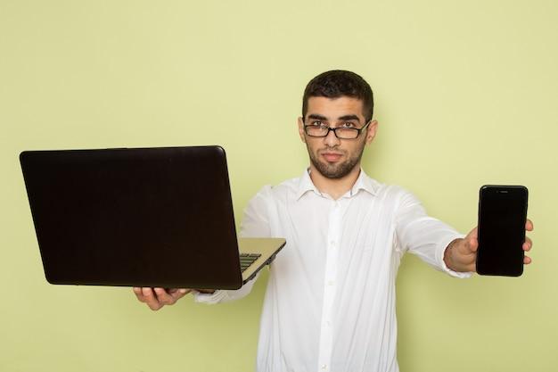 녹색 벽에 노트북과 휴대 전화를 들고 흰 셔츠에 남성 회사원의 전면보기