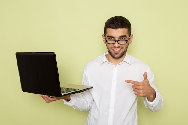 薄緑色の壁に笑みを浮かべてラップトップを保持している白いシャツの男性サラリーマンの正面図