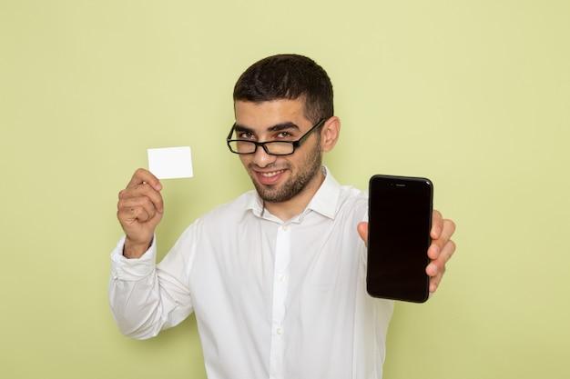 Вид спереди мужского офисного работника в белой рубашке, держащего смартфон и карту на светло-зеленой стене