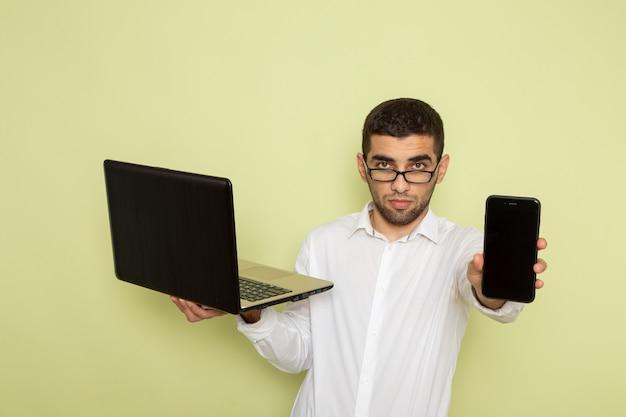 緑の壁にスマートフォンとラップトップを保持している白いシャツの男性サラリーマンの正面図
