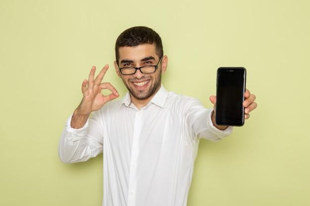 薄緑色の壁にスマートフォンを保持している白いシャツの男性サラリーマンの正面図