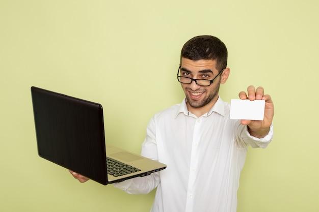 緑の壁に白いカードとラップトップを保持している白いシャツを着た男性サラリーマンの正面図
