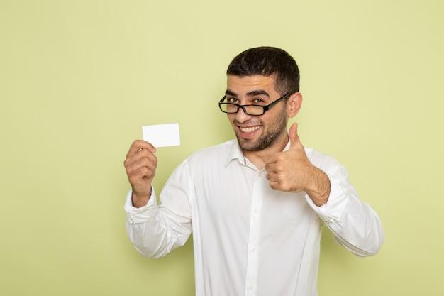 薄緑色の壁に白いプラスチックカードを保持している白いシャツを着た男性サラリーマンの正面図