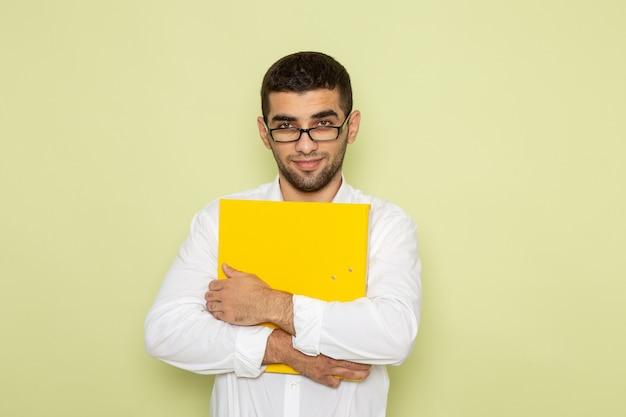 緑の壁に笑みを浮かべて黄色のファイルを保持している白いシャツの男性サラリーマンの正面図