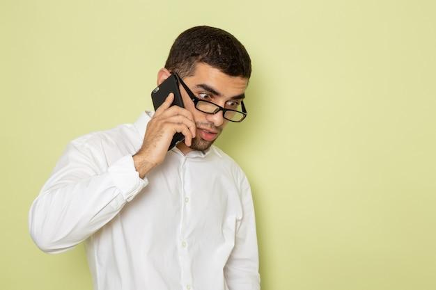 薄緑色の壁に電話で話している白いシャツを着た男性サラリーマンの正面図