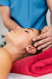 여성 환자의 목 척추를 검사하는 남성 정골 치료사의 전면보기