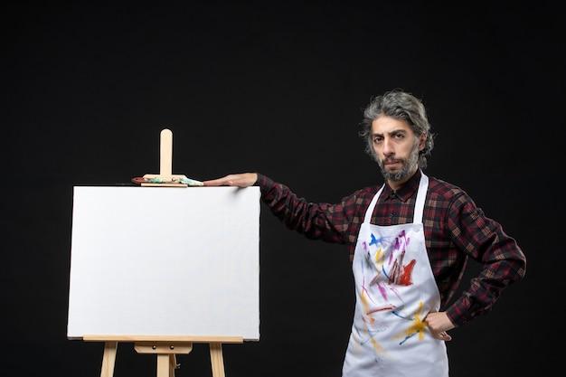 黒い壁に描くためのイーゼルと男性画家の正面図