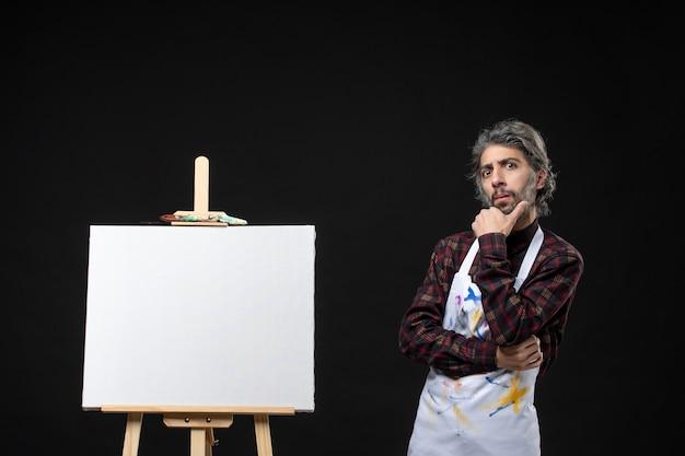 黒い壁にポーズを描くためのイーゼルと男性画家の正面図