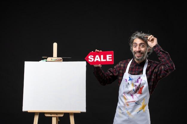 어두운 벽에 판매 배너를 들고 이젤을 가진 남성 화가의 전면 보기