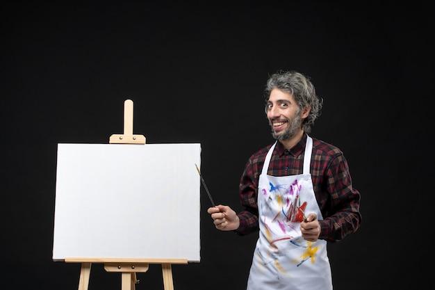 黒い壁に描くためのタッセルを保持しているイーゼルと男性画家の正面図
