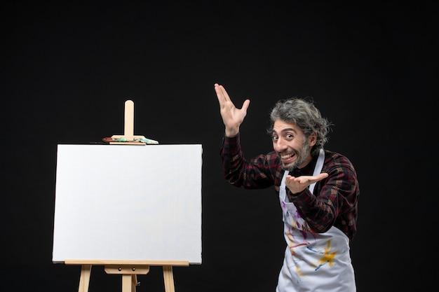 검은 벽에 이젤이 있는 남성 화가의 전면 모습