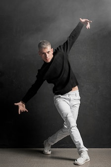 Вид спереди мужской исполнительницы в джинсах и кроссовках dacing
