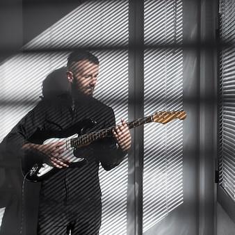 Мужчина-исполнитель играет на электрогитаре, вид спереди