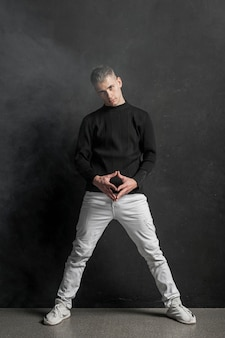 Вид спереди мужской исполнитель позирует в джинсах и кроссовках