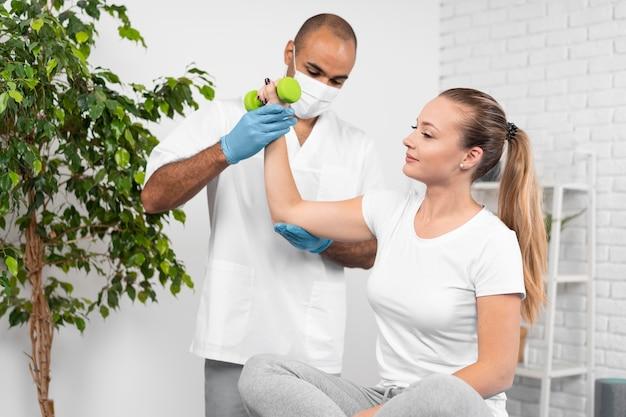 Вид спереди мужского физиотерапевта, проверяющего силу женщины