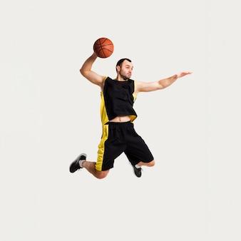 Вид спереди мужской игрок позирует в воздухе во время броска баскетбола
