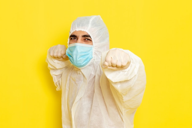 特別な防護服を着て、薄黄色の壁にマスクを付けた男性科学者の正面図