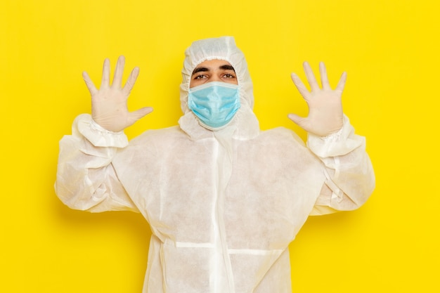 특수 보호 복 및 밝은 노란색 벽에 그의 손을 보여주는 마스크 남성 과학 노동자의 전면보기