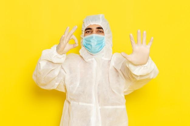 特別な防護服と薄黄色の壁に彼の手のひらを示すマスクと男性の科学者の正面図