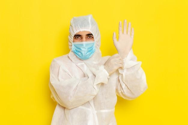 特別な防護服を着て、薄黄色の壁に手袋を着用したマスクを着用した男性科学者の正面図