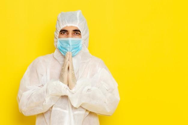 Вид спереди научного работника-мужчины в специальном защитном белом костюме и с маской, позирующей на желтой стене