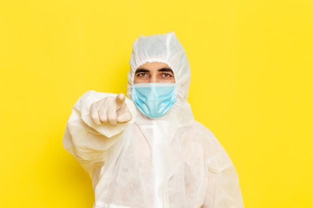 밝은 노란색 벽에 마스크와 특수 보호 흰색 정장에 남성 과학 노동자의 전면보기