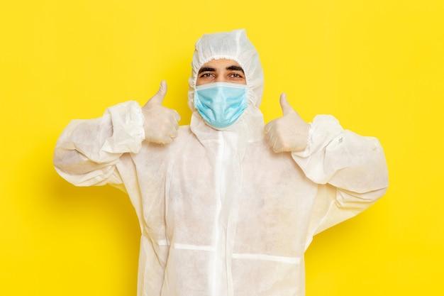 黄色の壁に笑みを浮かべてマスクと特別な保護白いスーツを着た男性科学者の正面図